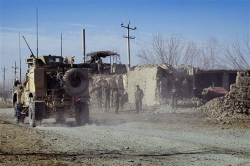 A U.S. military armored personal carrier vehicle passes by a damaged military check post after a suicide attack in Kunduz, north of Kabul, Afghanistan on Saturday, Dec. 11, 2010. A suicide bomber blew up a stolen police car that had been packed with explosives, injuring five Afghan soldiers and nine civilians near an army checkpoint in northern Afghanistan. (AP Photo/Fulad Hamdard)
